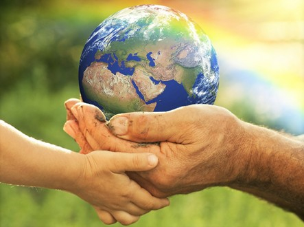 Senior man and baby holding the Earth in hands against a rainbow in spring. Ecology concept